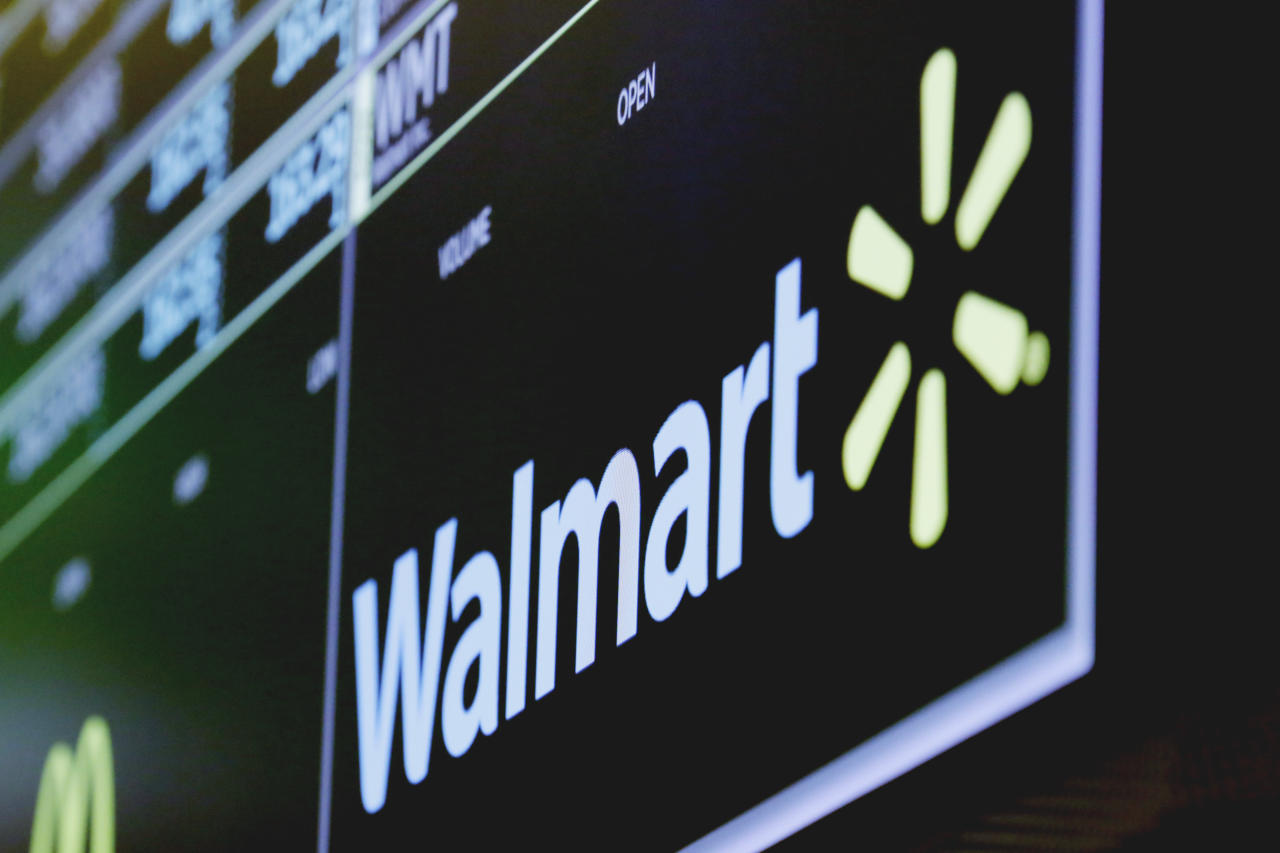 FILE- In this May 17, 2018, file photo the logo for Walmart appears above a trading post on the floor of the New York Stock Exchange. Walmart Inc. is making two improvements to its third-party marketplace heading into the holidays as it seeks to better compete with online leader Amazon.com. (AP Photo/Richard Drew, File)