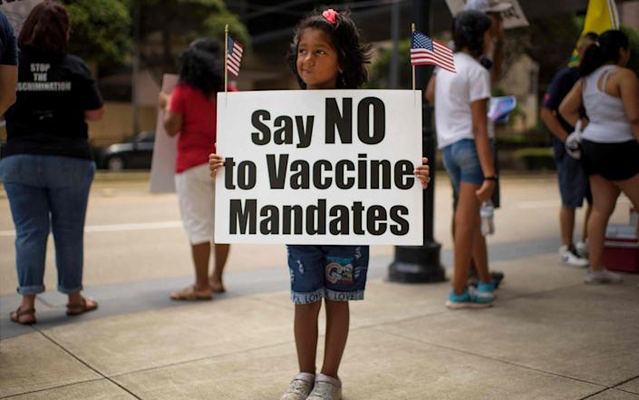 Anti-vaccine rally protesters hold signs outside of Houston Methodist Hospital - Mark Felix/AFP