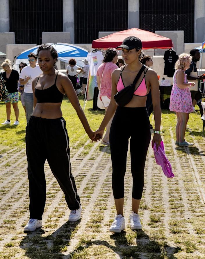 A couple, both in black pants and a sports bra, holds hands