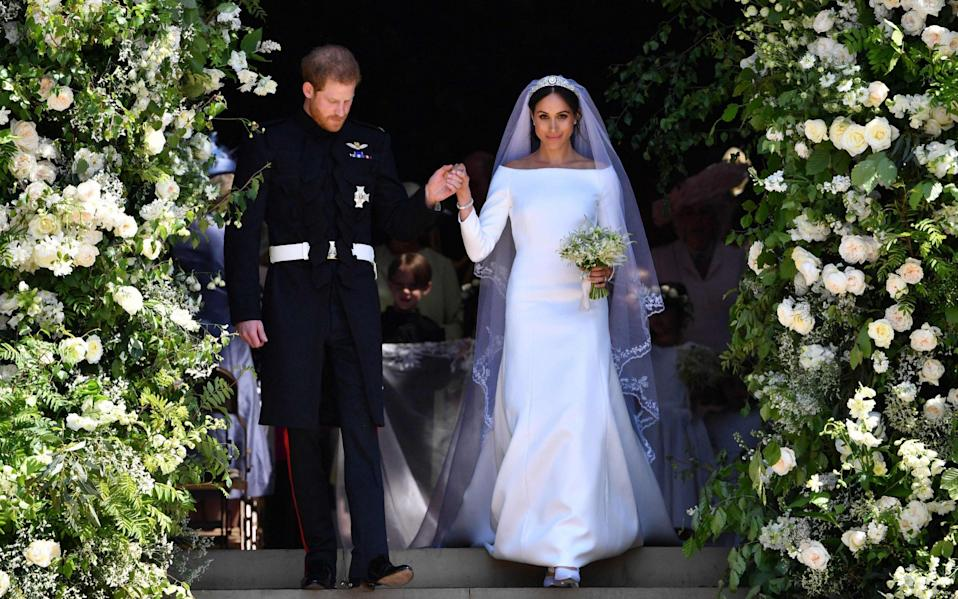 Harry, Duke of Sussex and his wife Meghan, Duchess of Sussex walk down the west steps of St George's Chapel, Windsor Castle, in Windsor, after their wedding ceremony - AFP/Ben Stansall