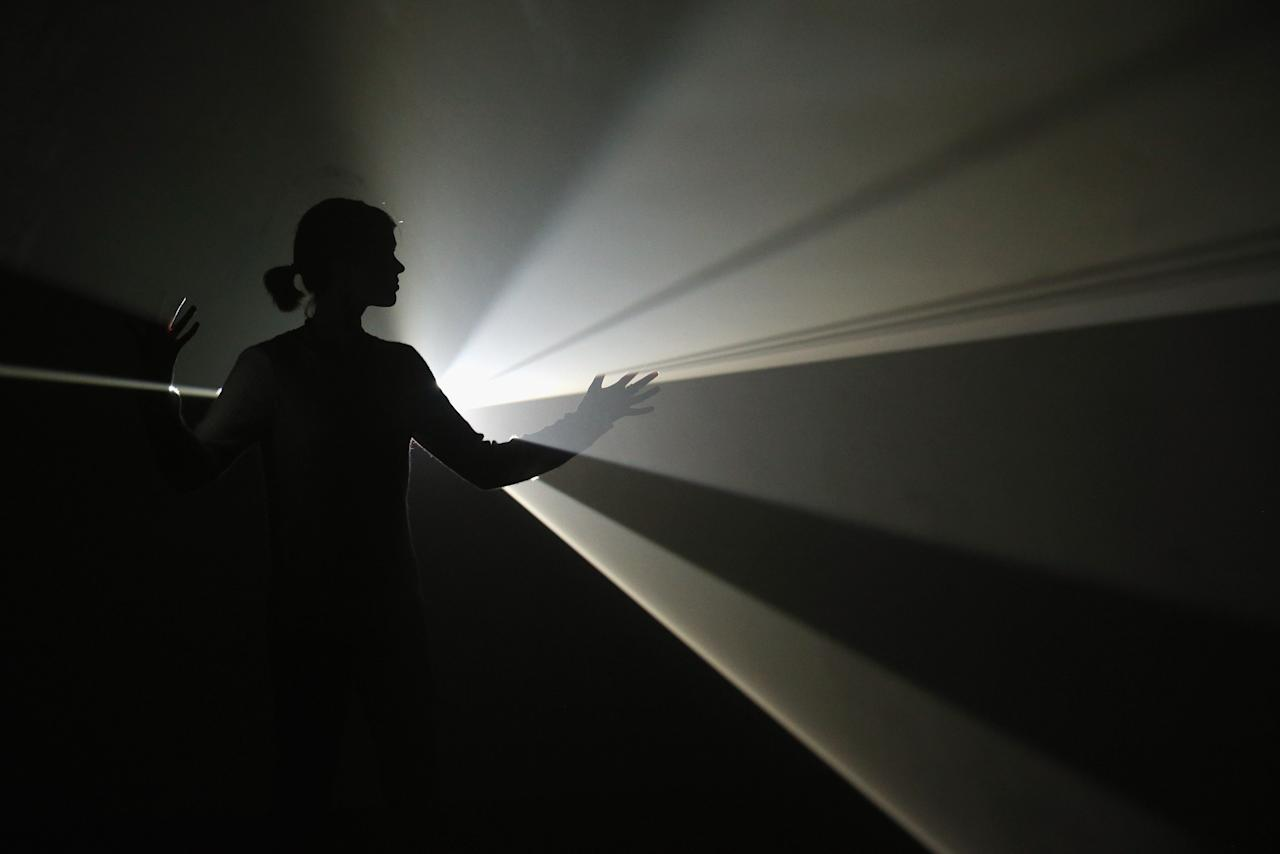 LONDON, ENGLAND - JANUARY 29:  A woman interacts with an art installation by Anthony McCall entitled 'You and I, Horizontal' which features in the Hayward Gallery's exhibition 'Light Show' on January 29, 2013 in London, England. 'Light Show' features 25 illuminated installations and sculptures by major international artists from the 1960s to the present day. The show opens to the general public on January 30, 2013 and runs until April 28, 2013.  (Photo by Oli Scarff/Getty Images)