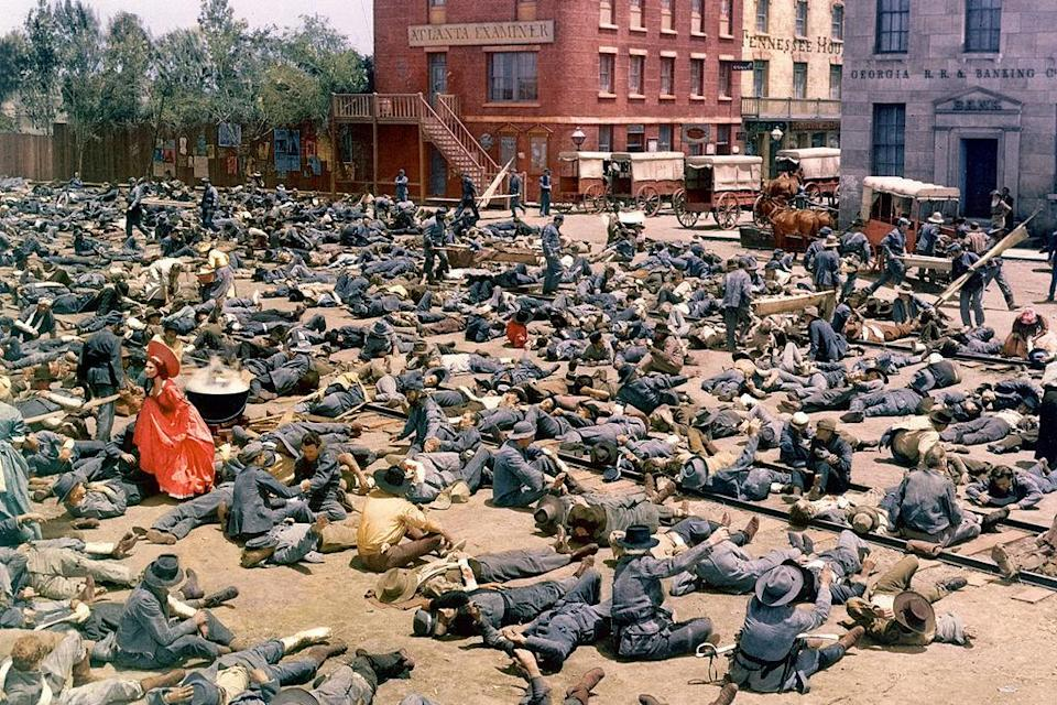 """<p>To replicate the devastation of the Civil War, Selznick wanted the body count to show for it - at the time, though, the Screen Actors Guild had a limited number of extras available. As an addendum to the 950 actors, the producer ordered <a rel=""""nofollow noopener"""" href=""""http://www.reelclassics.com/Movies/GWTW/gwtw-article.htm"""" target=""""_blank"""" data-ylk=""""slk:1,000 dummies"""" class=""""link rapid-noclick-resp"""">1,000 dummies</a> to fill in the Battle of Atlanta's dead and wounded; live actors manipulated the pretend ones to simulate writhing limbs. The trick worked. As the camera pans out on a stumbling Scarlett, more and more bodies fill the screen - with an aerial view of soldier's arms flailing and the sounds of moaning giving way to music, the train yard triage scene is as powerful as it is horrifying.</p>"""