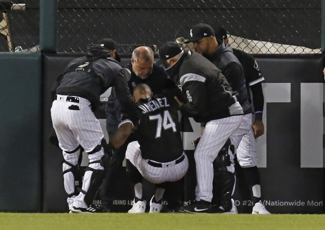 Chicago White Sox manager Rick Renteria, teammates and a team trainer help Eloy Jimenez (74) after he was injured while climbing the wall to go after a home run by Detroit Tigers' Grayson Greiner during the third inning of a baseball game Friday, April 26, 2019, in Chicago. (AP Photo/Nuccio DiNuzzo)