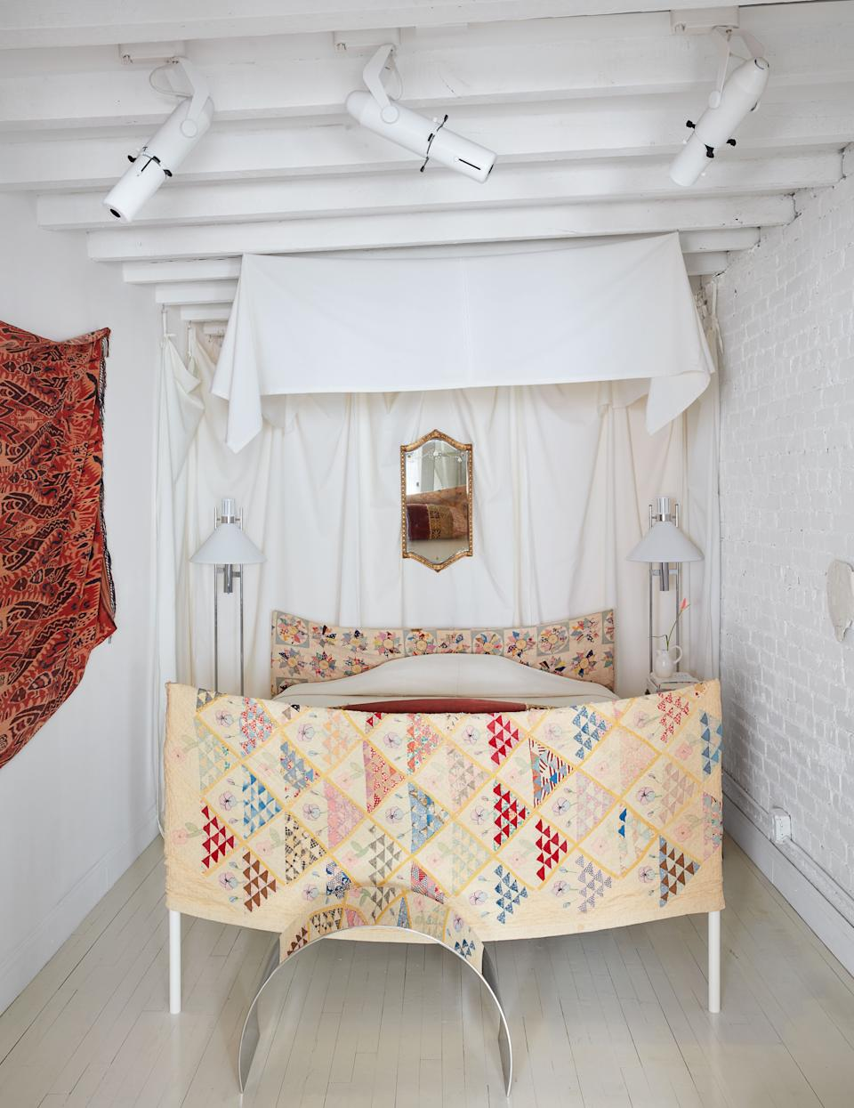 Vintage Robert Sonneman floor lamps flank the bed, which he slipcovered in a patchwork quilt.