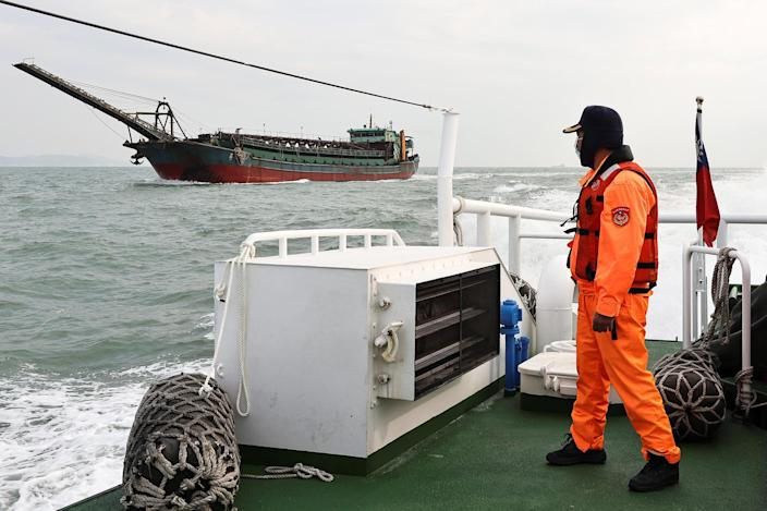Image: A Taiwanese coast guard looks at a sand-dredging ship with a Chinese flag in the waters off the Taiwan-controlled Matsu islands, on Jan. 28, 2021. (Ann Wang / Reuters)