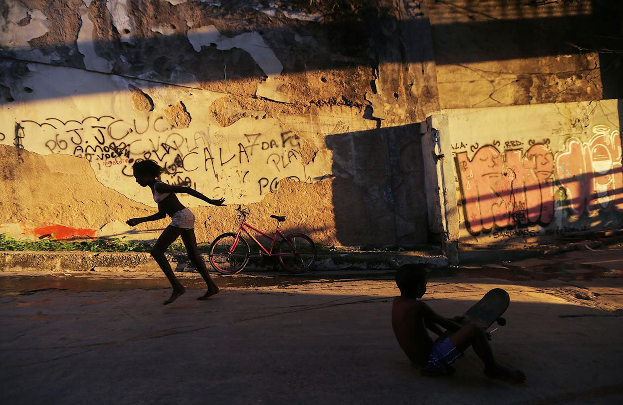 <p>Young residents play on a street passing through a set of buildings in the Mangueira favela (slum, in Portuguese) in Rio de Janeiro, May 4, 2017. Hundreds of residents who live in the occupied structures must collect water from hoses because of a shortage of running water in the buildings. A World Bank report released earlier this year states that Brazil's deep economic crisis could push up to 3.6 million people beneath the poverty line by the end of 2017. (Photo: Mario Tama/Getty Images) </p>
