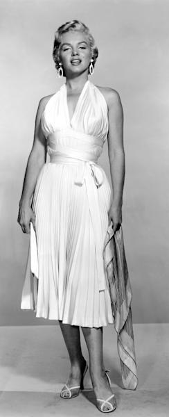 """In this undated publicity photo courtesy Running Press, Marilyn Monroe is shown in the first photo taken of her in the famous white dress from the """"The Seven Year Itch."""" For a brief scene in """"The Seven Year Itch,"""" in September 1954, her character strolls on a Manhattan street on a stifling summer evening. When a subway rattles beneath her, Marilyn stands astride a sidewalk vent to catch a cool breeze that swirls her skirt up around her waist. (AP Photo/Courtesy Running Press)"""