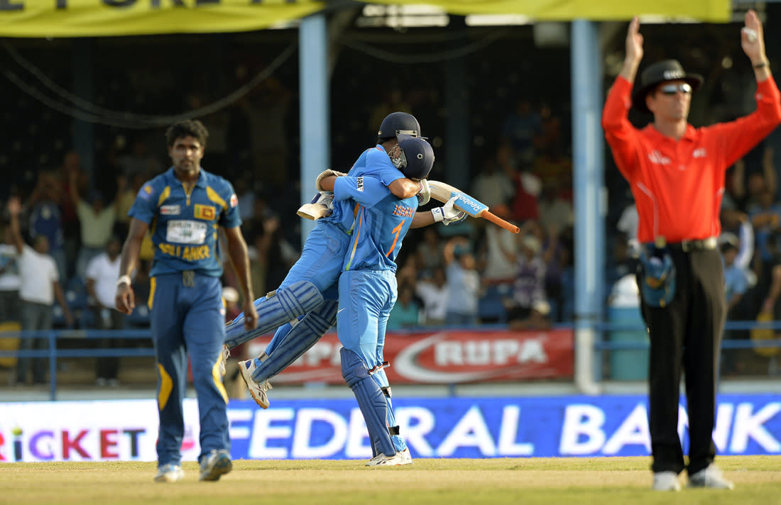 Indian cricket team captain Mahendra Sing Dhoni (C-L) is lifted off the ground by his teammate Ishant Sharma after hitting a boundary for six runs to seal their victory during the final match of the Tri-Nation series between India and Sri Lanka at the Queen's Park Oval stadium in Port of Spain on July 11, 2013. India defeated Sri Lanka by 1 wicket to win the series. AFP PHOTO/Jewel Samad