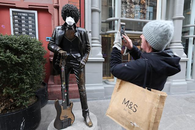A woman is pictured taking a photograph of the Phil Lynott Statue, complete with mask, off Grafton Street in Dublin. Ireland has had 366 confirmed cases. (Getty Images)