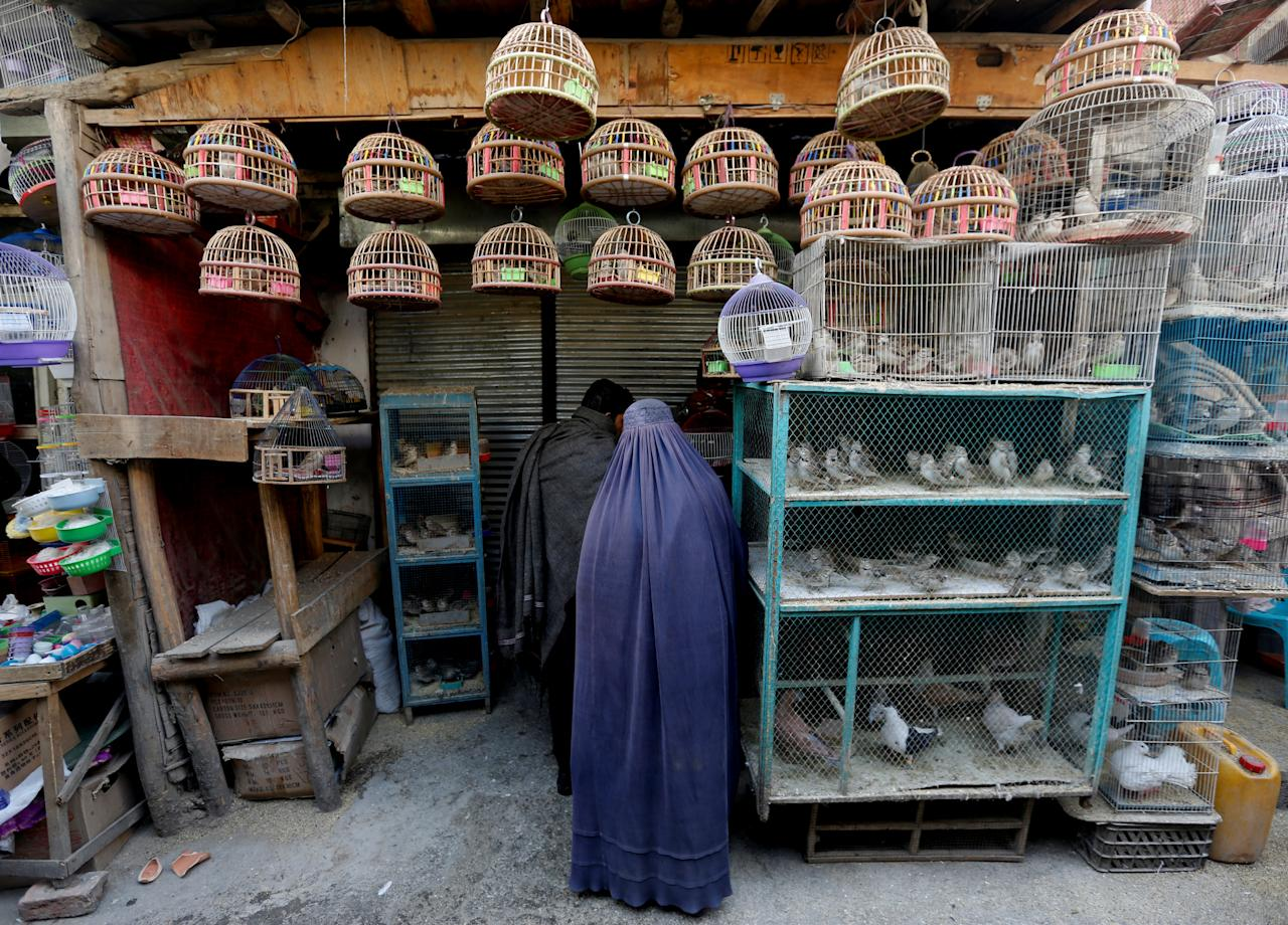 <p>An Afghan woman clad in burqa stands in front of a shop at Ka Faroshi bird market in Kabul, Afghanistan, Jan. 18, 2018. (Photo: Mohammad Ismail/Reuters) </p>