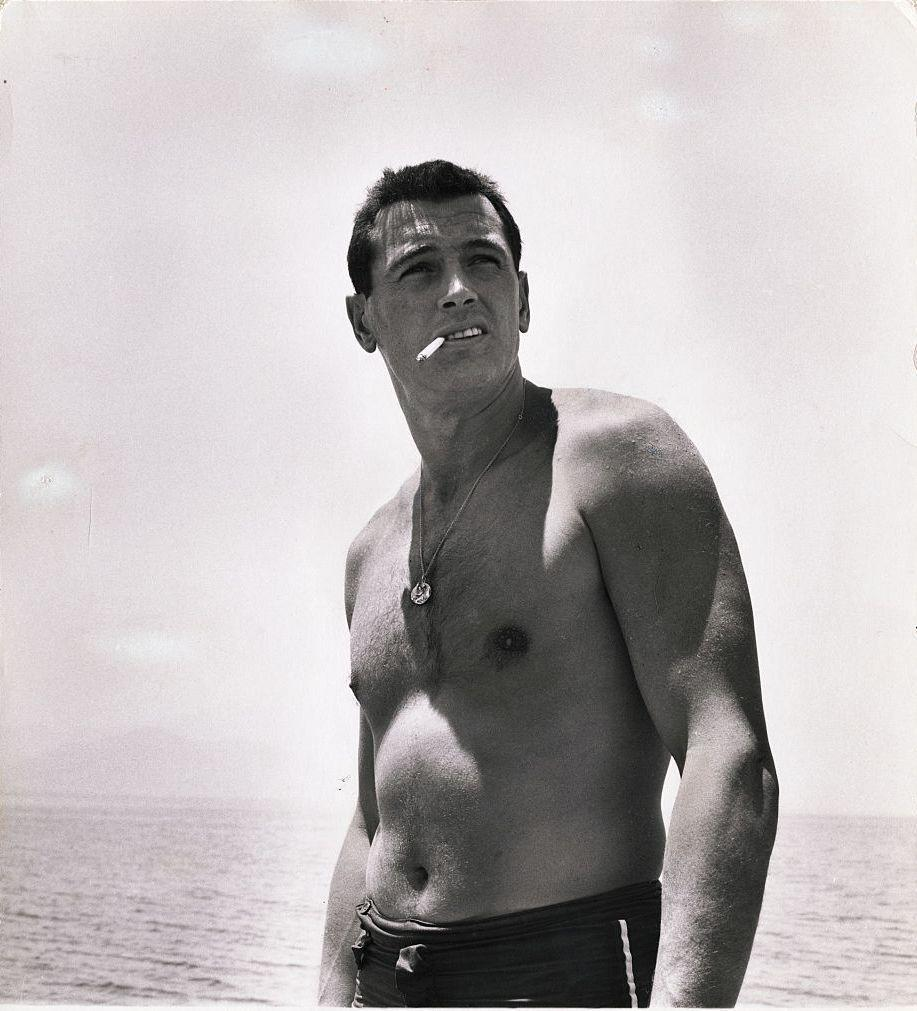 <p>Rock Hudson smokes a cigarette on the beach in 1940.</p>