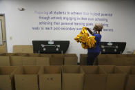 Stephanie Marshall, enrollment and marketing assistant at Agora Cyber Charter School, fills boxes with Agora supplies for family coaches to distribute to students, Wednesday, Aug. 4, 2021, in King of Prussia, Pa. (AP Photo/Jacqueline Larma)