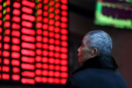 A man looks on in front of an electronic board showing stock information at a brokerage house in Nanjing