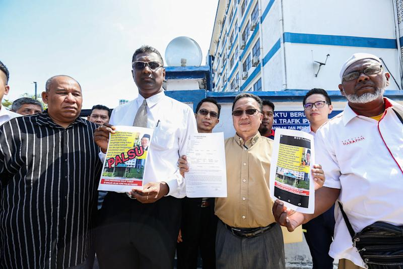 Lawyer RSN Rayer and information officer to the Penang chief minister Zahar Zainul show the police report and posters outside the Northeast District Police Station in George Town December 30, 2019. — Picture by Sayuti Zainudin