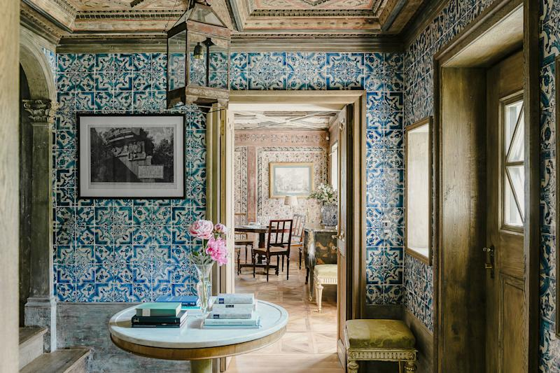 Blue-and-white Portuguese tiles from the 17th century cover the walls of the entry hall. Art by Giovanni Battista Piranesi; antique iron lantern.