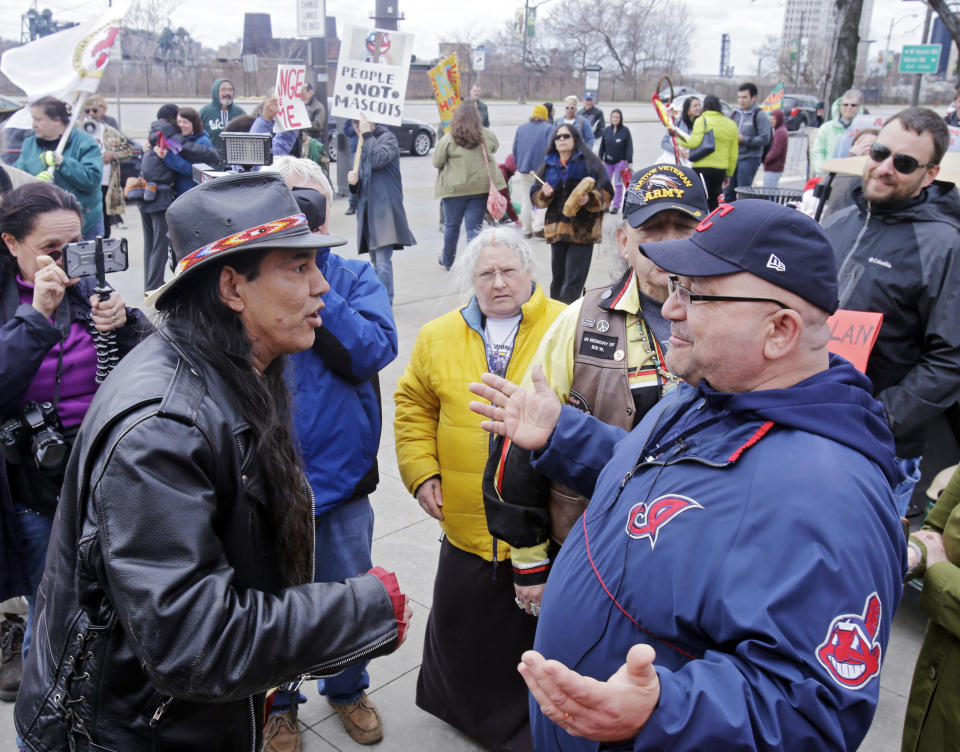 FILE - In this April 10, 2015, file photo, Philip Yenyo, left, executive director of the American Indians Movement for Ohio, talks with a Cleveland Indians fan before a baseball game against the Detroit Tigers, in Cleveland. The Cleveland Indians seem to be standing in an uncomfortable on-deck circle. Now that the NFL's Washington Redskins have retired their contentious nickname and logo after decades of objection and a recent uproar triggered by nationwide social protests, the Indians appear to be the next major sports franchise in line to change their identity. (AP Photo/Mark Duncan, File)