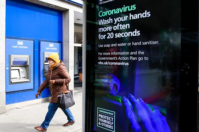 A woman walks past a coronavirus public information campaign poster in London. (PA)