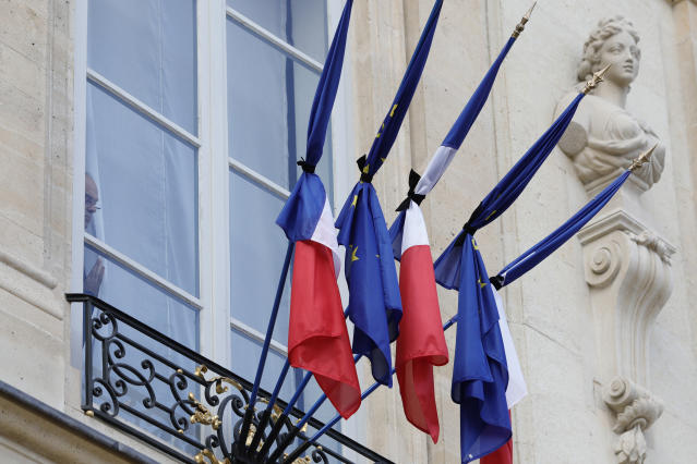 A man watches French and European flags at half-mast to pay homage to former French President Jacques Chirac, Friday Sept. 27, 2019 at the Elysee Palace in Paris. Jacques Chirac's death on Thursday at age 86 marked a nation feeling sorely in need of a leader with Chirac's staying power. (AP Photo/Kamil Zihnioglu)