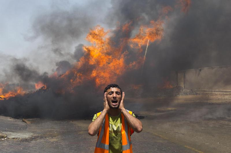 Palestinian firefighters try to extinguish fire after an Israeli military strike in an area west of Gaza City on July 12, 2014 (AFP Photo/Mahmud Hams)
