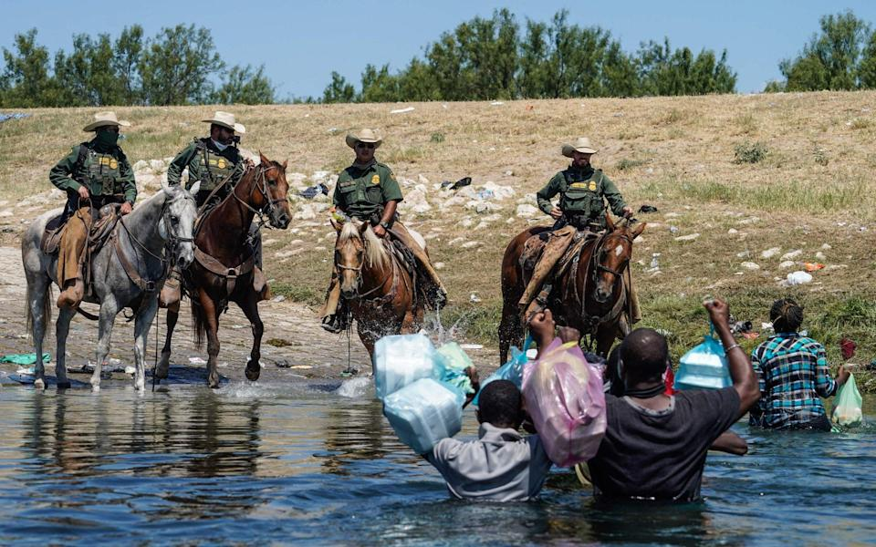 United States Border Patrol agents on horseback try to stop Haitian migrants from entering an encampment on the banks of the Rio Grande - PAUL RATJE/AFP via Getty Images