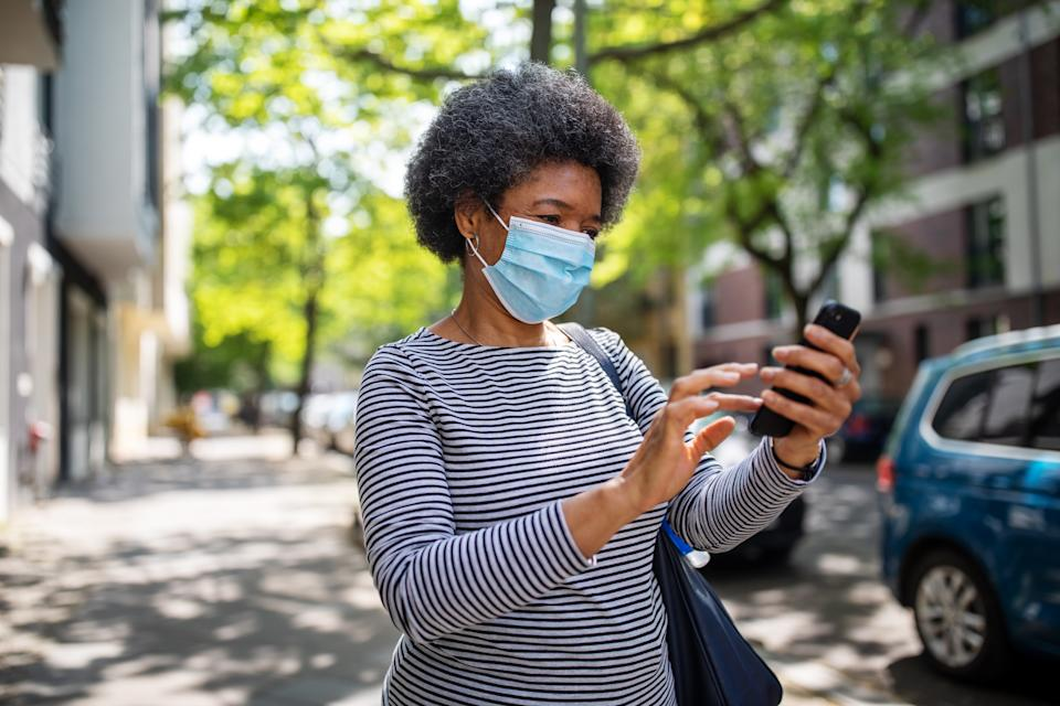 Mature woman wearing a medical mask walking in the city and texting on her phone. Woman walking on the empty street during corona virus outbreak using her mobile phone.
