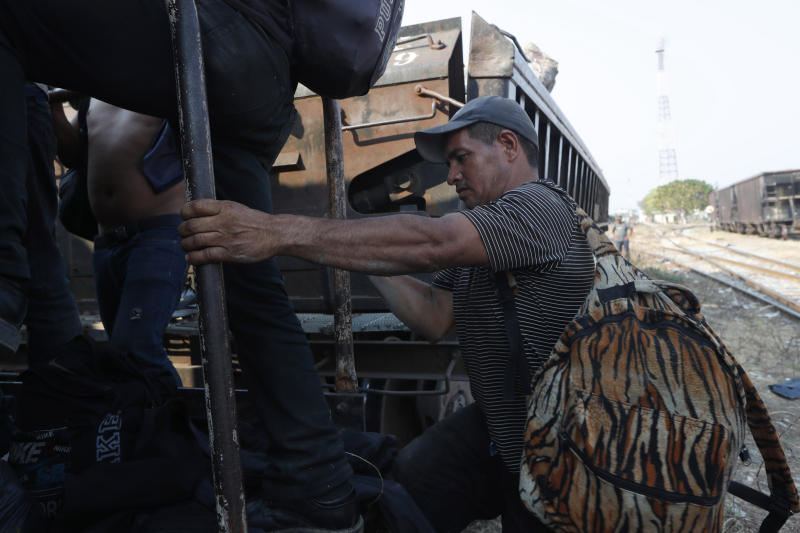 """A Central American migrant climbs on a freight train on is way to the U.S.-Mexico border, in Ixtepec, Oaxaca state, Mexico, Tuesday, April 23, 2019. The train known in Spanish as """"La Bestia"""" has carried migrants north for decades, despite its notorious dangers. People have died or lost limbs falling from the train. (AP Photo/Moises Castillo)"""