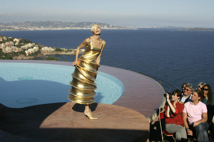 FILE - In this Oct.6, 2008 file photo, a model wears a creation by French fashion designer Pierre Cardin during the presentation of his entire Spring-Summer 2009 and Autumn-Winter 2009 collections at his villa in Theoule sur Mer, southern France.Pierre Cardin, the French designer whose famous name embossed myriad consumer products after his iconic Space Age styles shot him into the fashion stratosphere in the 1960s, has died, the French Academy of Fine Arts said Tuesday. He was 98. (AP Photo/Lionel Cironneau, File)
