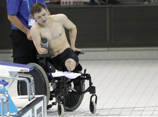 Lyndon Longhorne gets into his wheelchair after breaking the British record for his S4 class and securing his qualification for the 2012 London Paralympics after the multi classification men's 150m individual medley final at the British Gas Swimming Championships 2012 at the Olympic Aquatics Centre in London March 8, 2012.