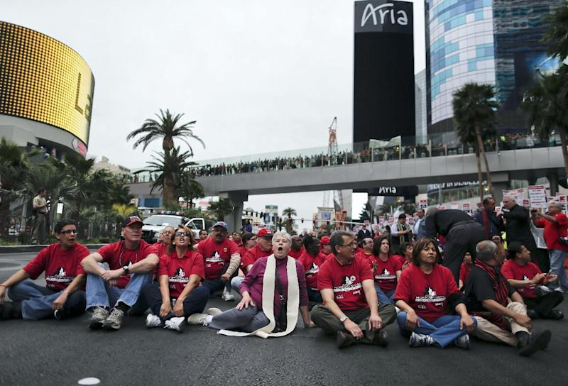 Protestors sit on Las Vegas Boulevard outside the Cosmopolitan Hotel and Casino blocking traffic as an act of civil disobedience while protesting their contract negotiations with Deutsche Bank, Wednesday, March 20, 2013, in Las Vegas. Nearly 98 protestors were arrested during the demonstration. Workers have been in contract talks with Cosmopolitan Las Vegas owner Deutsche Bank for two years. (AP Photo/Julie Jacobson)