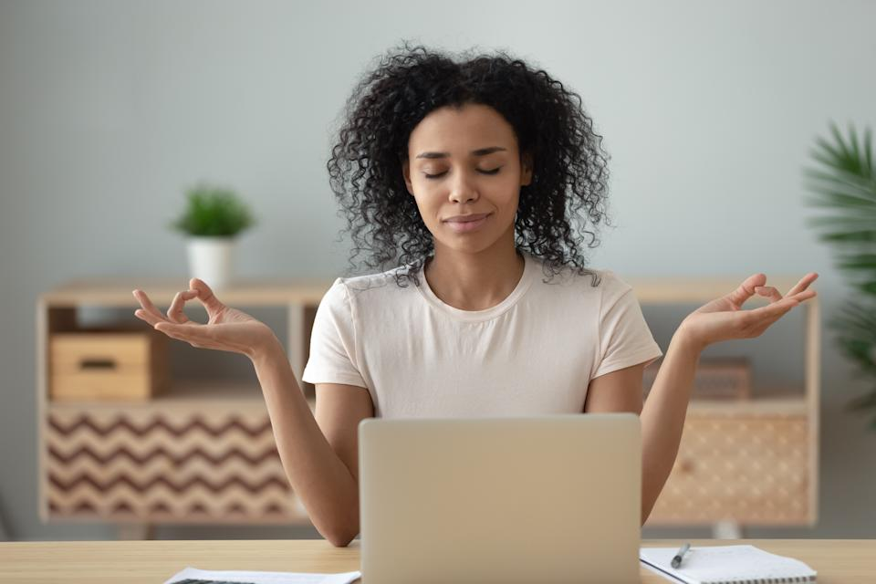 African woman meditating sit at desk in front of pc, serene mixed-race female closed eyes folded fingers mudra symbol do exercise practising yoga reducing anxiety stress positive frame of mind concept