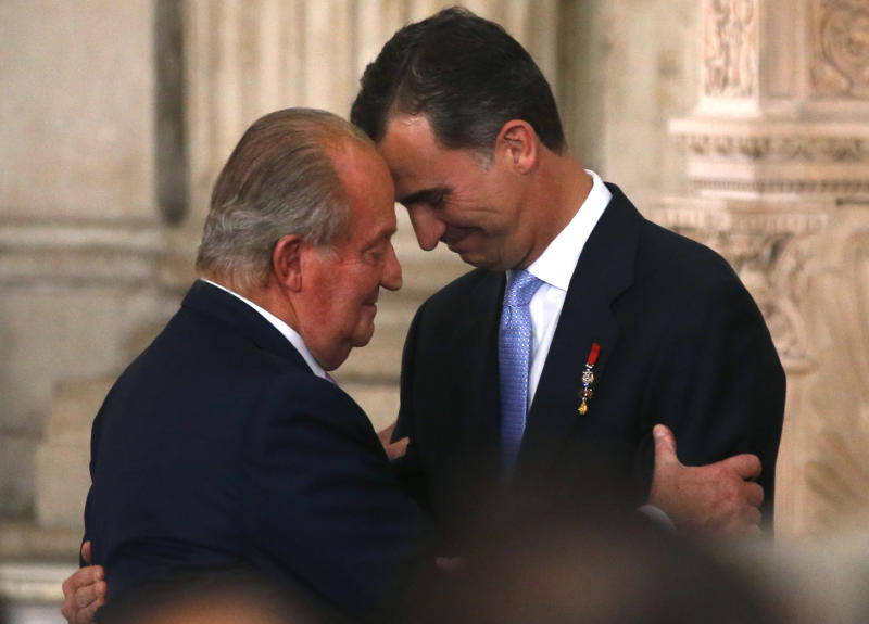 Spain's King Juan Carlos and his son Crown Prince Felipe (R) hug each other as they attend the signature ceremony of the act of abdication at the Royal Palace in Madrid, June 18, 2014. King Juan Carlos said on June 2 he would abdicate in favour of his son Prince Felipe, aiming to revive the scandal-hit monarchy at a time of economic hardship and growing discontent with the wider political elite. REUTERS/Juan Medina (SPAIN - Tags: POLITICS ROYALS ENTERTAINMENT TPX IMAGES OF THE DAY)