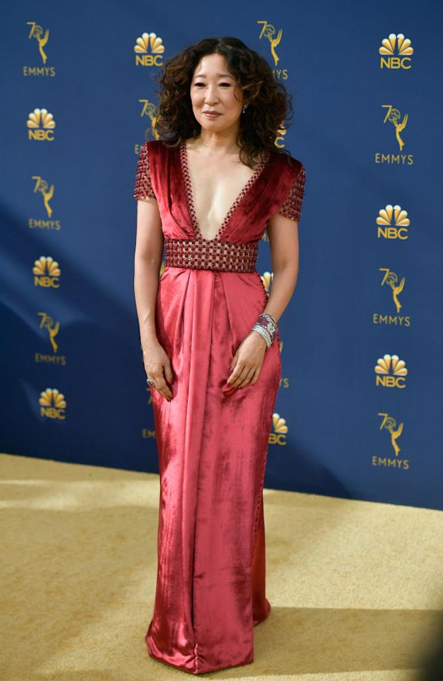 <p>Sandra Oh stunned in a shiny red floor-length gown with beaded detailing. The actress showed some skin thanks to a deep V-neckline and unlined beading around the waist. Her signature curls were even more voluminous than usual. Oh's parents were by her side to support her as the first Asian actor ever to earn a nomination in the Lead Actress category. (Photo: Frazer Harrison/Getty Images) </p>