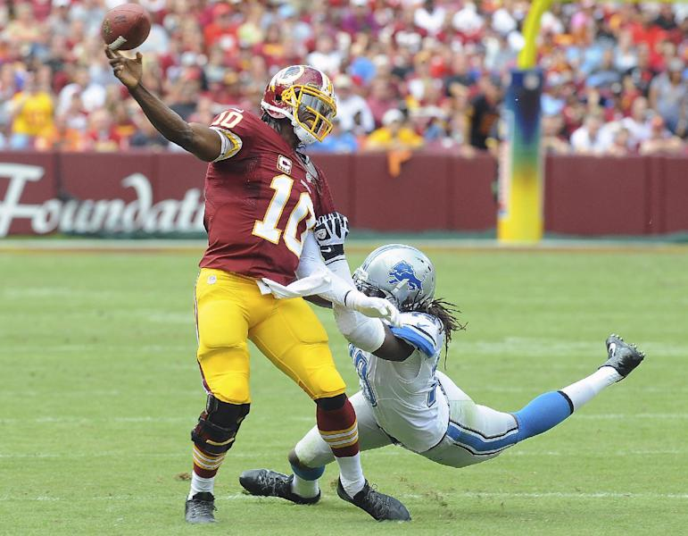 Washington Redskins quarterback Robert Griffin III is pulled to the turf by Detroit Lions defensive end Willie Young during the first half of a NFL football game in Landover, Md., Sunday, Sept. 22, 2013. (AP Photo/Richard Lipski)