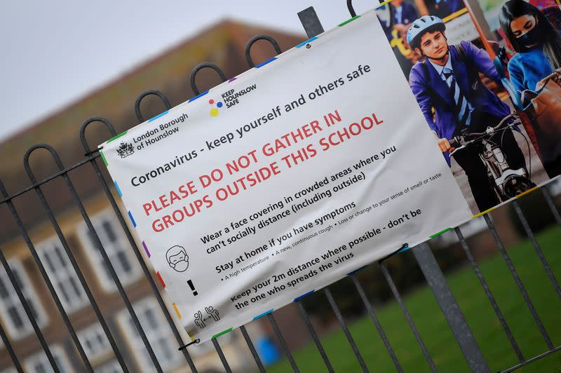 A social distancing health message is seen outside of a secondary school in London