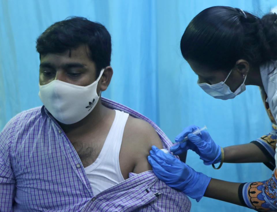 A health worker inoculates a school teacher Mohammed Haseeb Khan with the vaccine for COVID-19 during a special drive for teachers and students in Mumbai, India, Tuesday, Sept. 28, 2021. (AP Photo/Rajanish kakade)