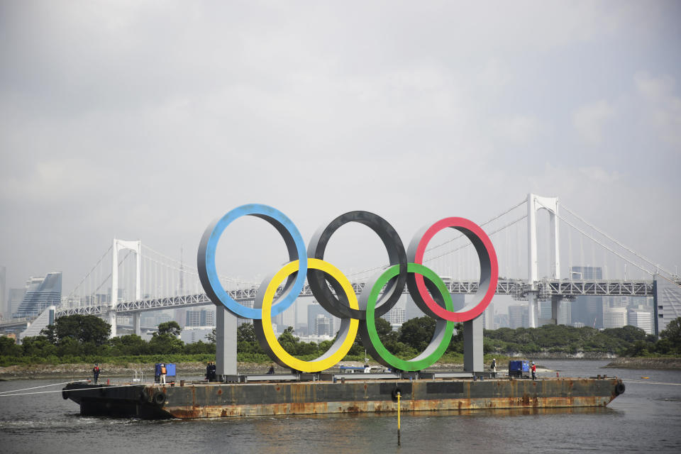 """A symbol installed for the Olympic and Paralympic Games Tokyo 2020 on a barge is moved away from its usual spot by tugboats off the Odaiba Marine Park in Tokyo Thursday, Aug. 6, 2020. The five Olympic rings floating on a barge in Tokyo Bay were removed for what is being called """"maintenance,"""" and officials says they will return to greet next year's Games. The Tokyo Olympics have been postponed for a year because of the coronavirus pandemic and are to open on July 23, 2021. The Paralympics follow on Aug. 24. (AP Photo/Hiro Komae)"""