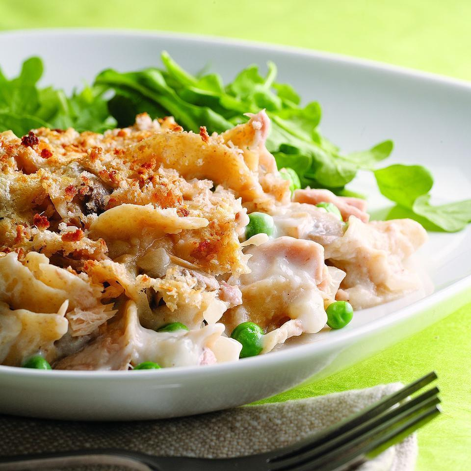 <p>Known as Tuna-Pea Wiggle to some, this family-friendly tuna noodle casserole tends to be made with canned soup and whole milk, which means high fat and sodium. We remedy this by making our own creamy mushroom sauce with nonfat milk thickened with a bit of flour. Look for whole-wheat egg noodles--they have more fiber than regular egg noodles (but this dish will work well and taste great with either).</p>