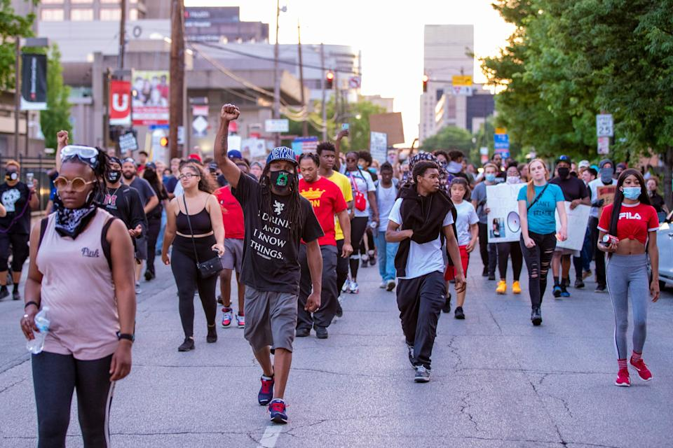 Protesters make their way through downtown Louisville during a demonstration on June 16, 2020.