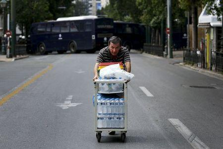 A man pushes a trolley with bottles of drinking water for sale on a deserted street during demonstrations in Athens, Greece, June 30, 2015. REUTERS/Yannis Behrakis