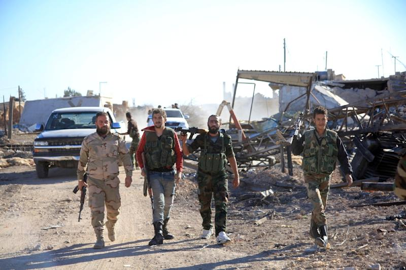 A group of Syrian pro-government fighters walk in the village of Sheikh Ahmad near the Kweyris military air base, east of the Syrian province of Aleppo on November 10, 2015 (AFP Photo/George Ourfalian)