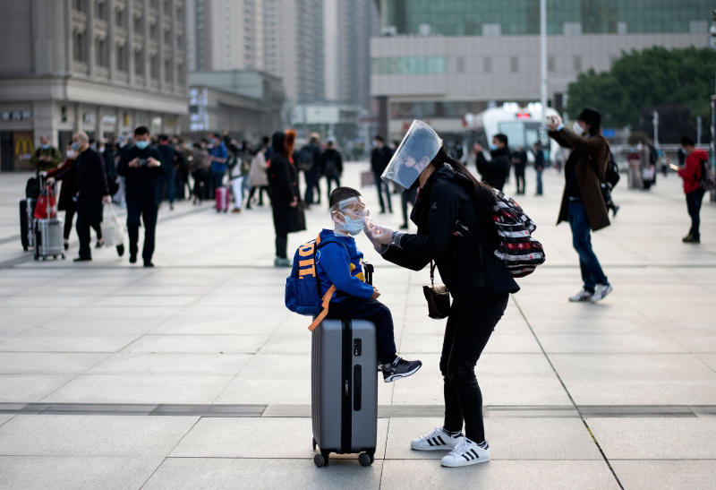 Image: A woman wearing a face mask adjusts her child's mask as they arrive at Hankou Railway Station in Wuhan to take one of the first trains leaving the city in China's central Hubei province (Noel Celis / AFP - Getty Images)