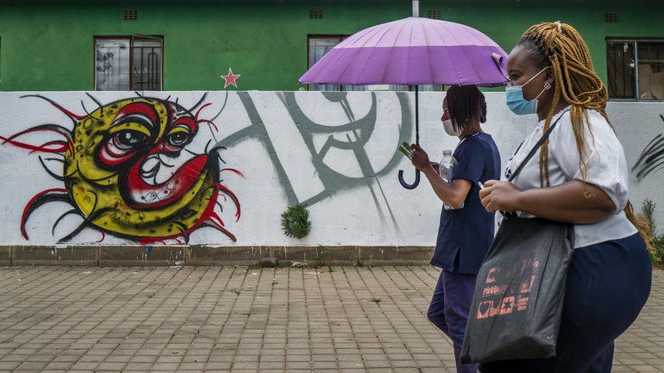 """Two women walk past a COVID-19 graffiti in Soweto's Orlando West township near Johannesburg, South Africa, Thursday Nov. 19, 2020. Africa has surpassed 2 million confirmed coronavirus cases as the continent's top public health official warns that """"we are inevitably edging toward a second wave"""" of infections. The 54-nation continent of 1.3 billion people is being warned against """"prevention fatigue"""" as countries loosen pandemic restrictions to ease their economies' suffering and more people travel. (AP Photo/Jerome Delay)"""