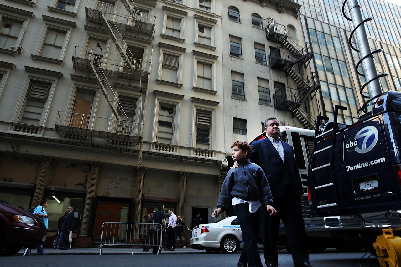 NEW YORK, NY - APRIL 26: People walk by a building on Park Place in lower Manhattan where a piece of landing gear believed to be from one of the planes destroyed in the September 11 attacks has been discovered on April 26, 2013 in New York City. The landing gear was discovered wedged between a mosque site and a  building blocks from the World Trade Center site.  (Photo by Spencer Platt/Getty Images)