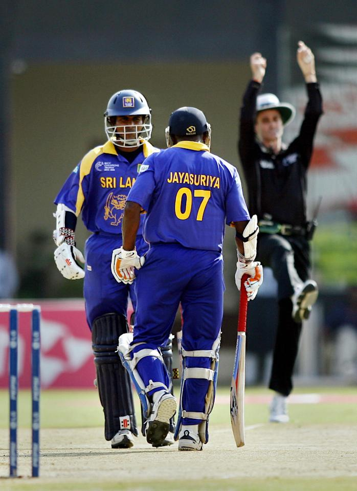 Jaipur, INDIA:  Sri Lankan cricketer Sanath Jayasuriya (C) walks towards teammate Upul Tharanga (L) after he hit a boundary signalled by the umpire (R), during an ICC Champions Trophy 2006 match at The Sawai Man Singh Stadium in Jaipur, 17 October 2006.  Sri Lanka captain Mahela Jayawardene elected to bat after winning the toss against Pakistan in a Group B match of the Champions Trophy tournament.  AFP PHOTO/Christophe ARCHAMBAULT  (Photo credit should read CHRISTOPHE ARCHAMBAULT/AFP/Getty Images)