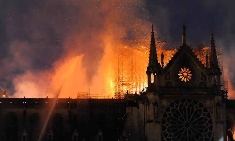 Firefighters tackle the blaze as the roof of Notre Dame burns