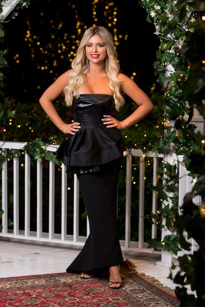 Monique Morley poses in a black strapless dress on The Bachelor
