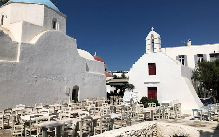 Empty tables greet the few tourist in Mykonos