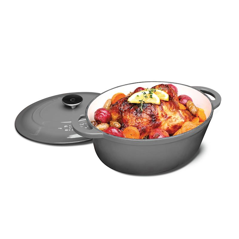 Gray cast iron French oven with roast chicken inside