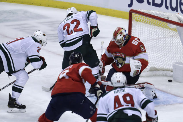Minnesota Wild defenseman Carson Soucy, left, scores a goal against goaltender Chris Driedger (60) during the third period of an NHL hockey game, Tuesday, Dec. 3, 2019, in Sunrise, Fla. The Wild won 4-2. (AP Photo/Lynne Sladky)