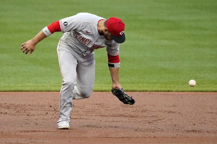 Cincinnati Reds third baseman Eugenio Suarez misplays a ball allowing Pittsburgh Pirates' Anthony Alford to reach base during the first inning of a baseball game in Pittsburgh, Tuesday, Sept. 14, 2021. (AP Photo/Gene J. Puskar)